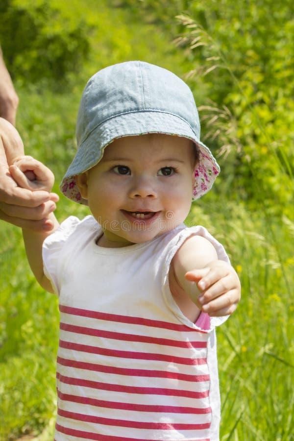 Poco bebé camina con su mano en la cámara Un niño camina en un prado florecido, retrato vertical Retrato soleado de imagen de archivo