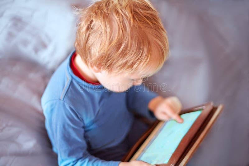 Poco bebé caucásico se sienta en el sofá usando una tableta, pantalla táctil Pelo rojo, ropa de sport, dentro, cierre para arriba fotografía de archivo