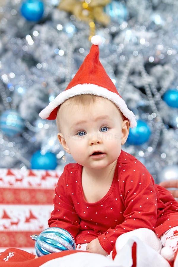 Poco bebé de la Navidad en el traje de Papá Noel El niño que sostiene la bola azul cerca de día de fiesta enciende el fondo fotografía de archivo libre de regalías