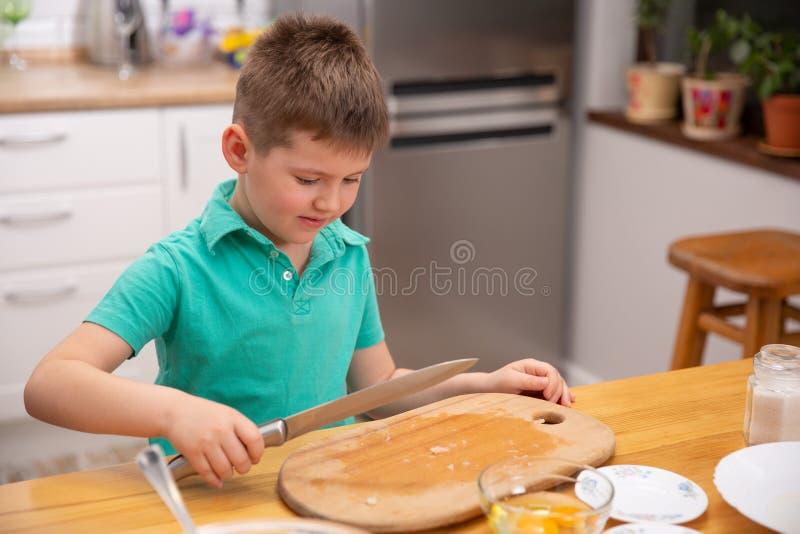 Poco bebé está alcanzando el cuchillo de cocina - peligro en cocina fotografía de archivo