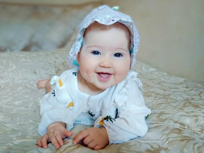 Poco bebé hermoso en una cama beige fotografía de archivo