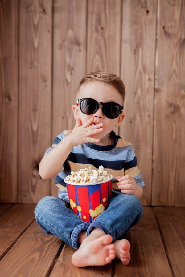 Poco bebé lindo del niño 2-3 años, vidrios del cine del imax 3d que sostienen el cubo para las palomitas, comiendo los alimentos  foto de archivo