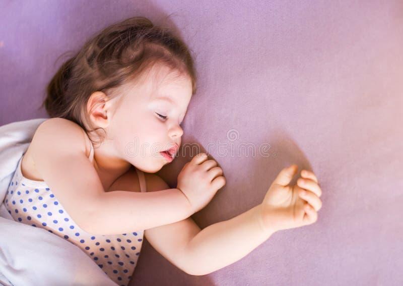Poco bebé lindo que duerme a fondo en su cama fotografía de archivo