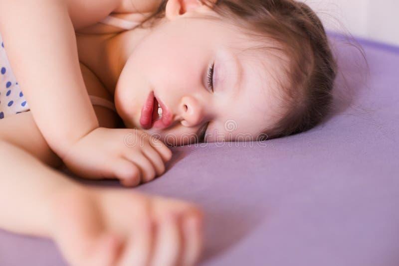 Poco bebé lindo que duerme a fondo en su cama fotos de archivo