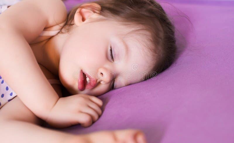 Poco bebé lindo que duerme a fondo en su cama fotografía de archivo libre de regalías