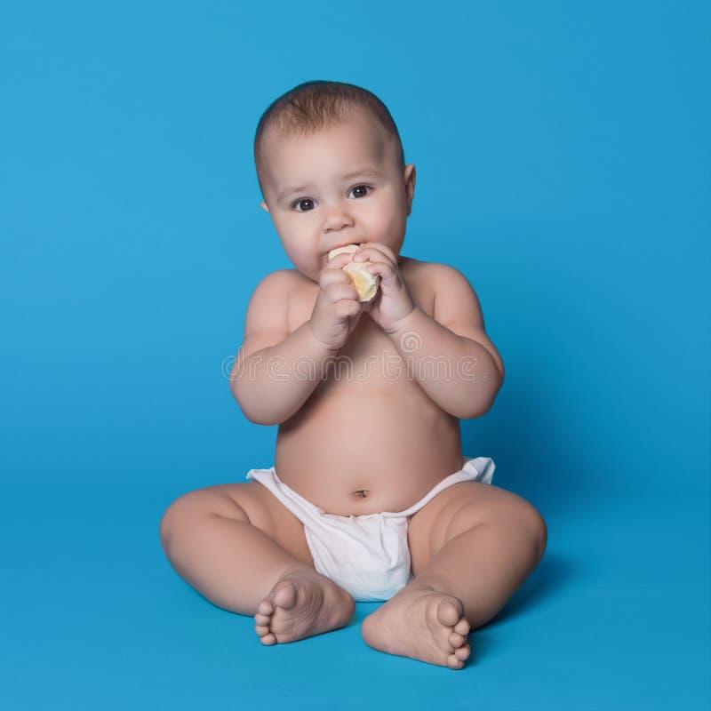 Poco bebé que come el plátano fresco en fondo azul imágenes de archivo libres de regalías