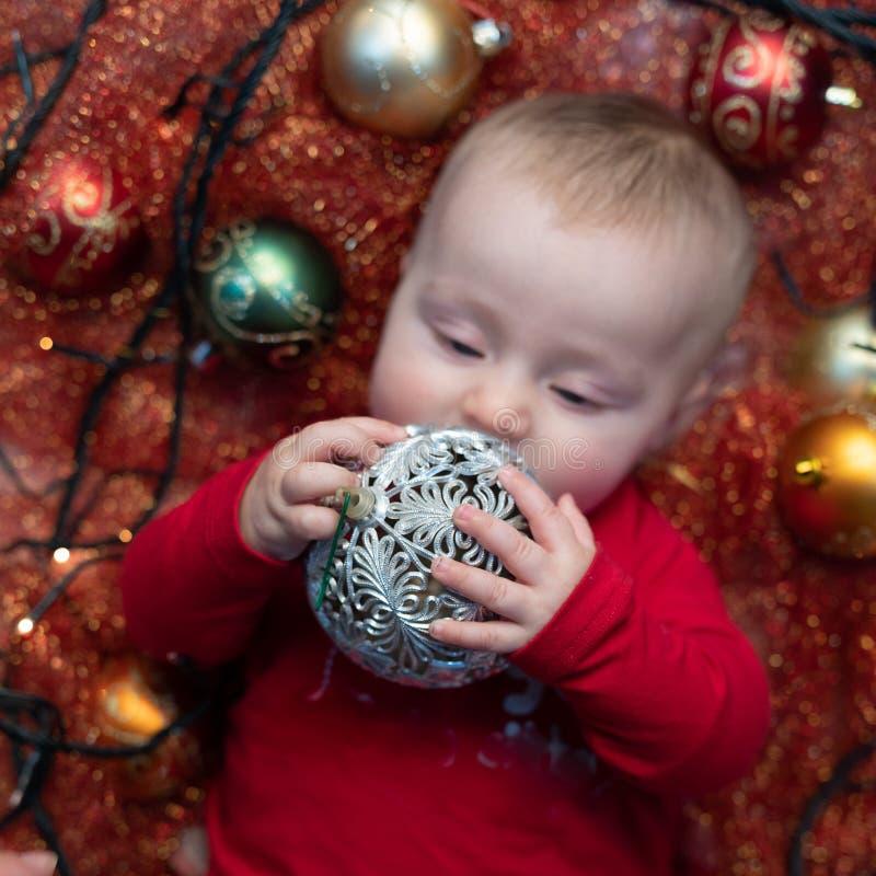 Poco bebé que juega con una chuchería de la Navidad imagen de archivo libre de regalías