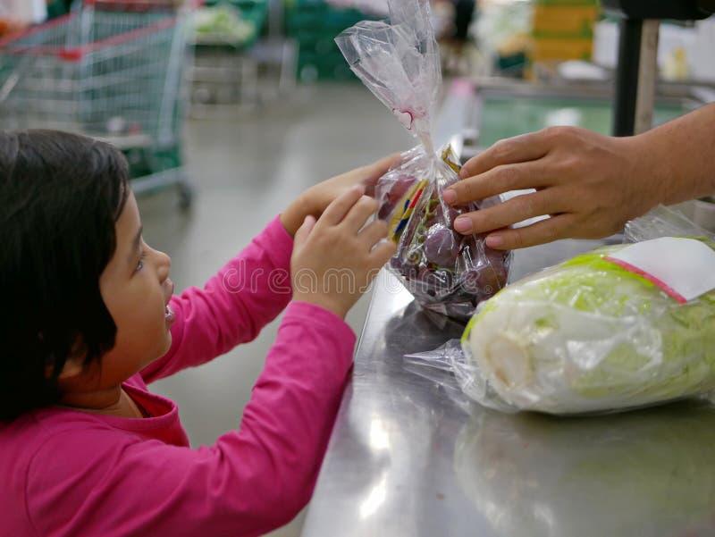 Poco bebé que recibe un paquete de uvas y de una col del contador después de que fueran pesados y calculados el precio imagen de archivo libre de regalías