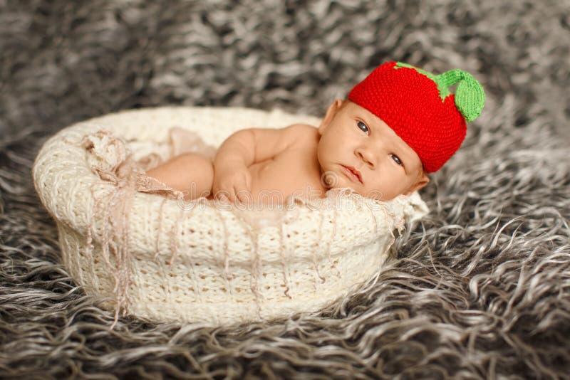 Poco bebé recién nacido en un sombrero divertido que duerme en la manta blanca, LY fotografía de archivo