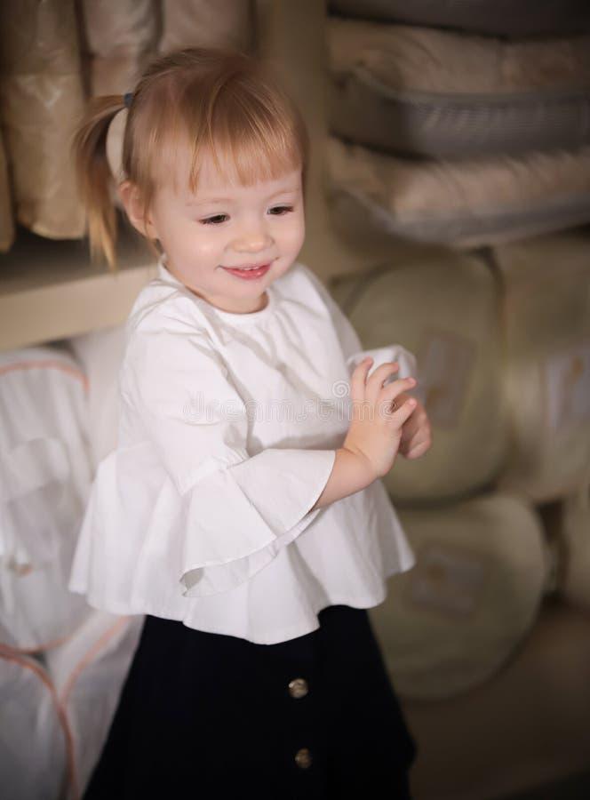 Poco bebé rubio feliz en la tienda de la materia textil Sonrisa imágenes de archivo libres de regalías