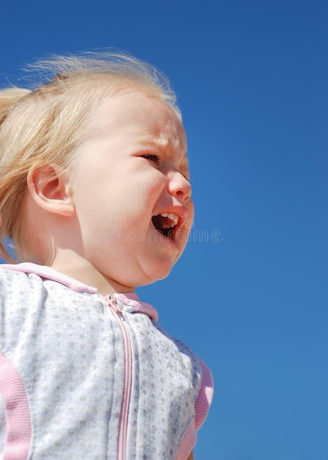 Poco beb? que llora en el fondo del cielo azul imagen de archivo libre de regalías