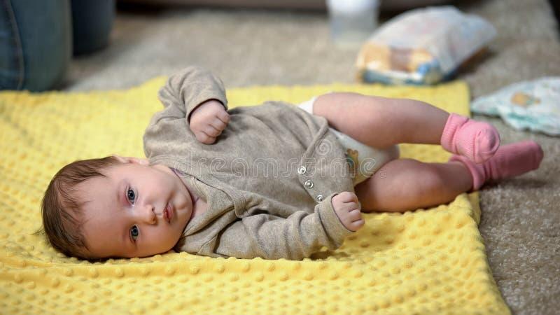 Poco beb? que miente solamente en la drenaje-hoja mientras que la madre est? ocupada, falta de tiempo imágenes de archivo libres de regalías
