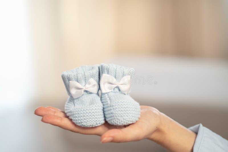 Poco calcetines hechos punto azules con un arco en la mano de la mujer embarazada Concepto del embarazo y de la paternidad fotografía de archivo libre de regalías