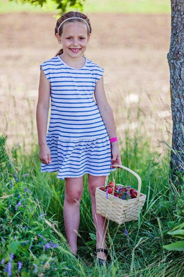 Poco canestro della tenuta della ragazza della scuola in pieno delle fragole all'azienda agricola di raccolto di auto fotografia stock