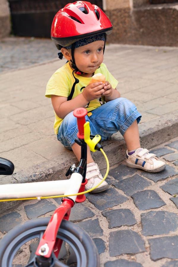 Poco conductor de la bicicleta que come el helado imágenes de archivo libres de regalías