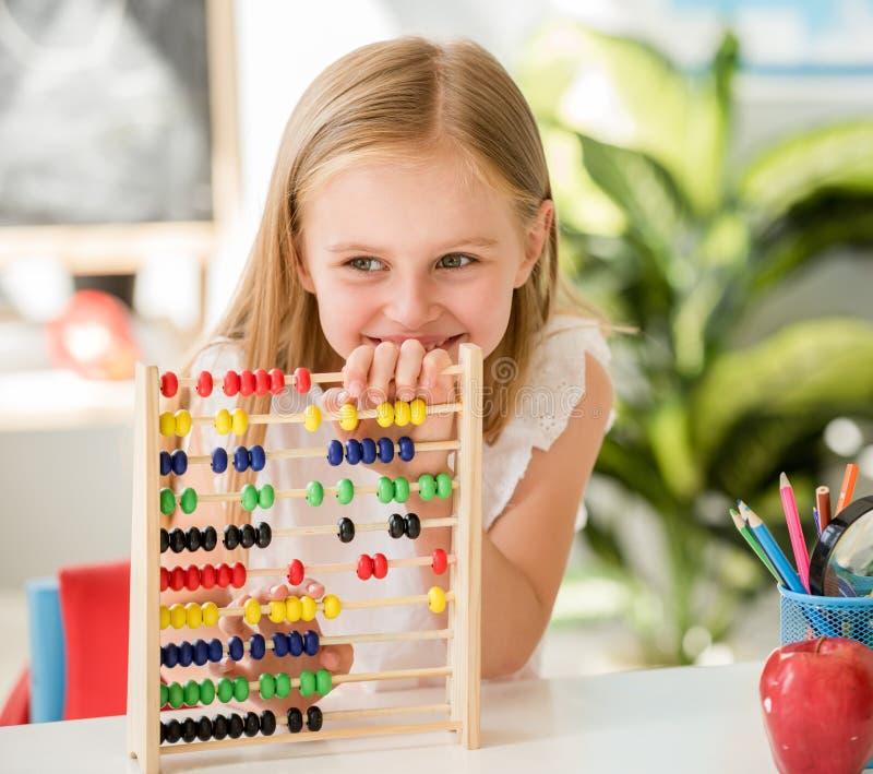 Poco contando en el ábaco colorido en la sala de clase de la escuela imagen de archivo libre de regalías