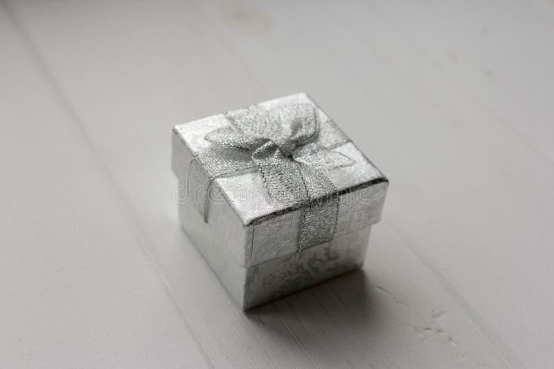 Poco contenitore di regalo d'argento sui precedenti di legno bianchi immagini stock libere da diritti