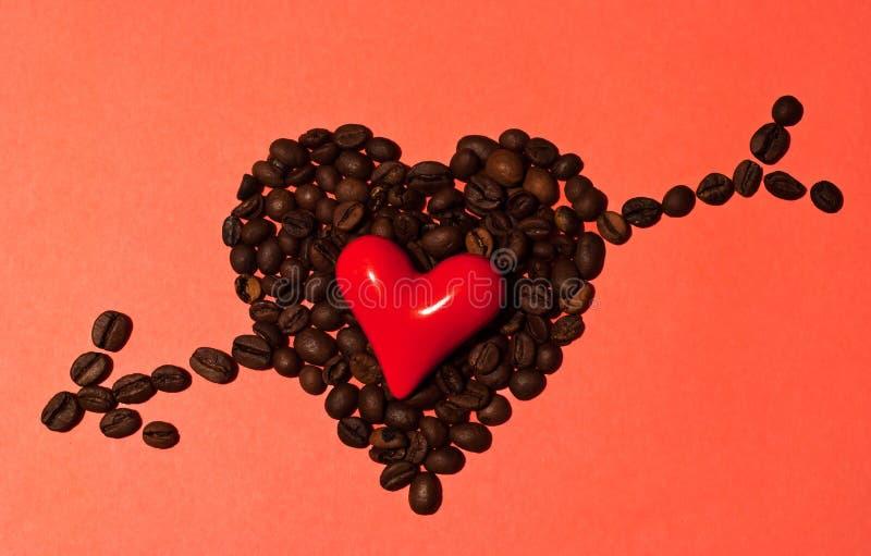 Poco corazón rojo con los granos de café fotografía de archivo libre de regalías
