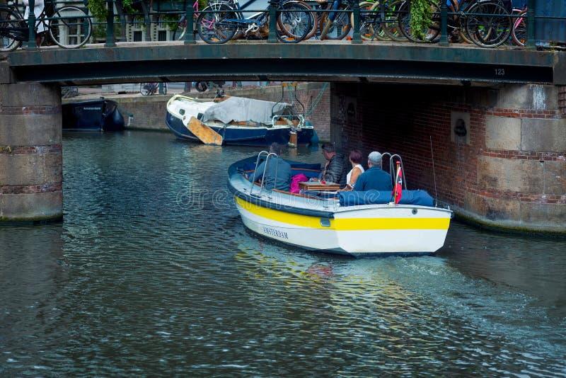 Poco crogiolo di canale che passa sotto un ponte, Amsterdam, Paesi Bassi fotografia stock libera da diritti
