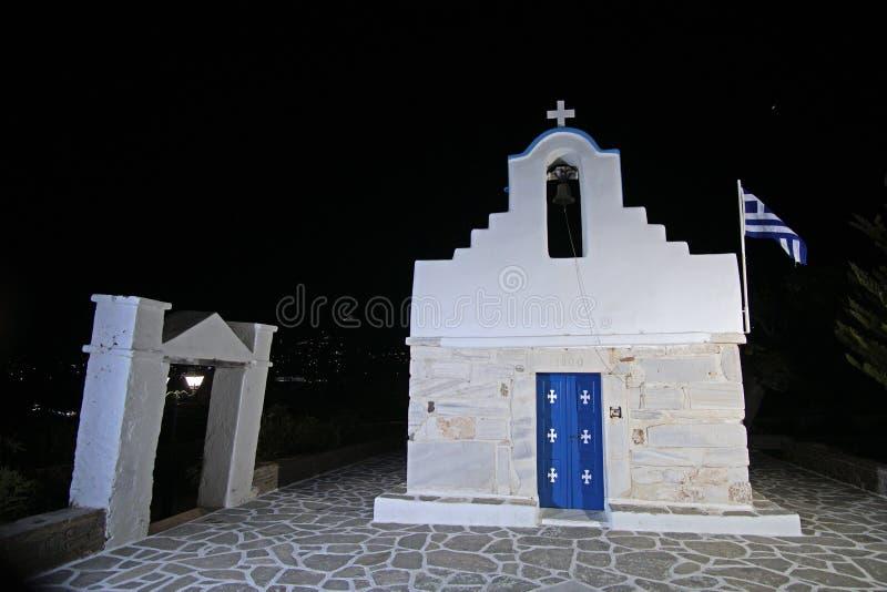 Poco cuadrado con la iglesia típica con la bóveda azul y bandera griega en la isla de Paros, Cícladas, Grecia fotos de archivo