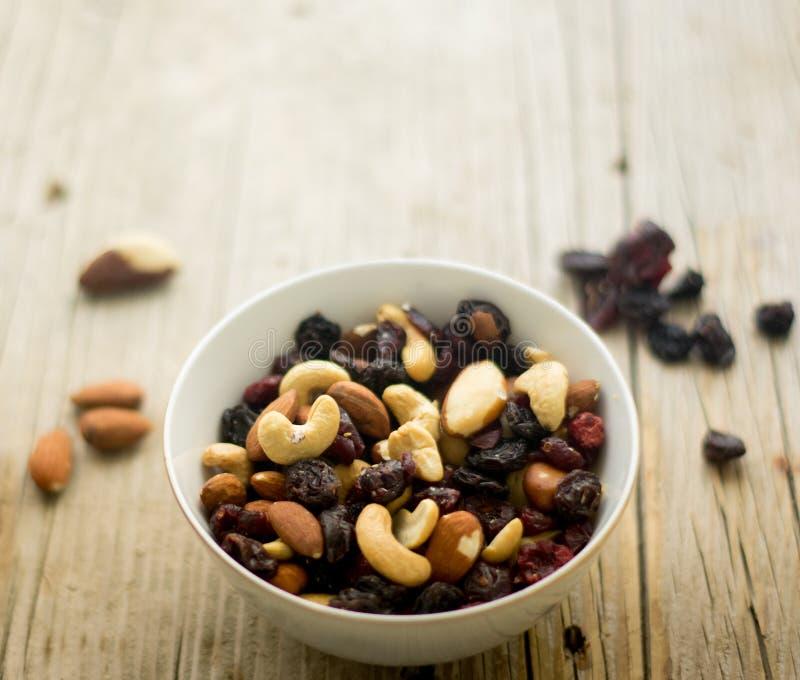 Poco cuenco con las nueces mezcladas y las frutas secadas en la tabla de madera foto de archivo libre de regalías