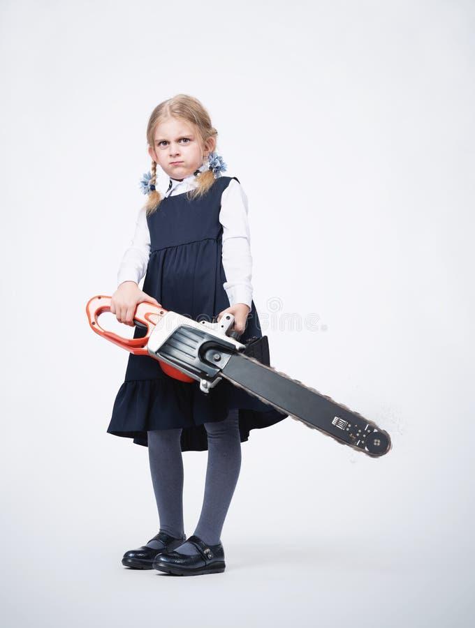 Poco descontentó a la muchacha confiada en uniforme escolar sostiene una sierra eléctrica de trabajo en sus manos Concepto de la  imagen de archivo libre de regalías