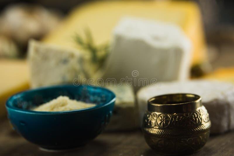 Poco diferente tipo de quesos con las aceitunas papel y el aceite de oliva en la pizarra negra en cocina fotos de archivo libres de regalías
