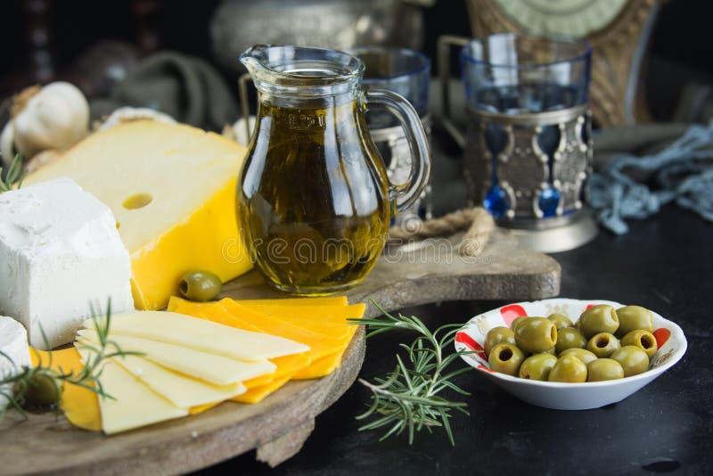 Poco diferente tipo de quesos con las aceitunas papel y el aceite de oliva en la pizarra negra en cocina foto de archivo