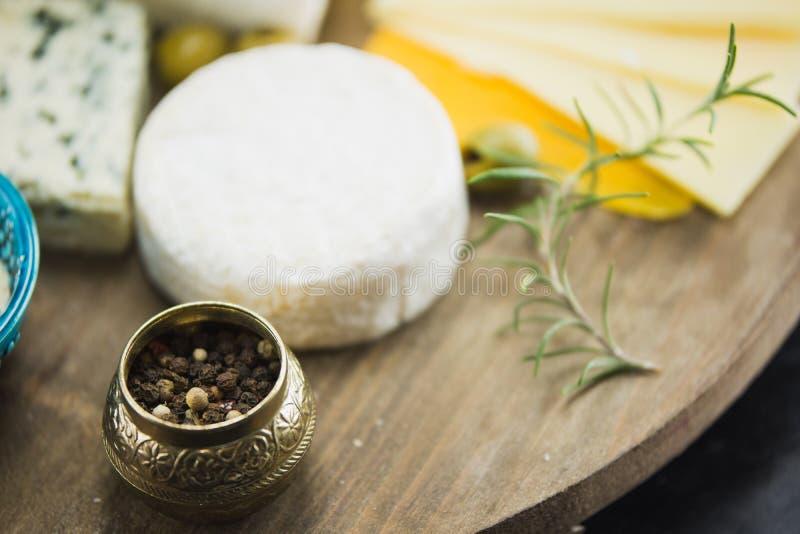 Poco diferente tipo de quesos con las aceitunas papel y el aceite de oliva en la pizarra negra en cocina imagenes de archivo