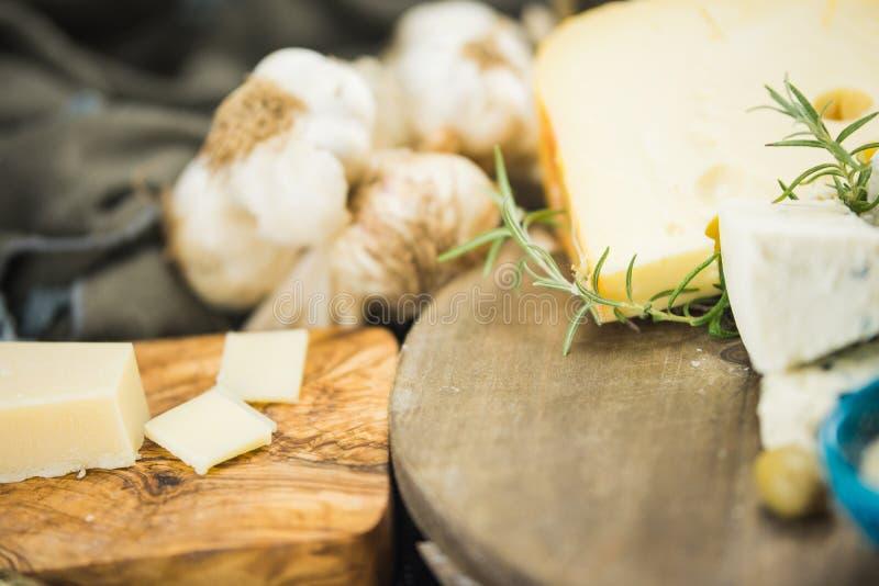 Poco diferente tipo de quesos con las aceitunas papel y el aceite de oliva en la pizarra negra en cocina fotografía de archivo
