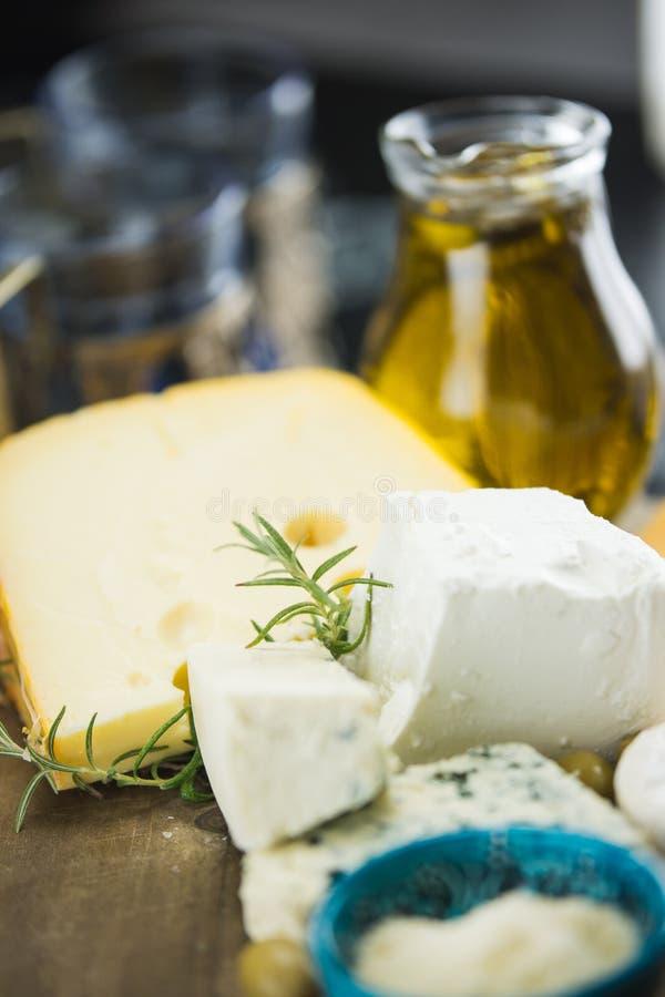 Poco diferente tipo de quesos con las aceitunas papel y el aceite de oliva en la pizarra negra en cocina foto de archivo libre de regalías