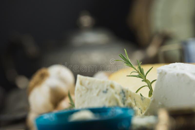 Poco diferente tipo de quesos con las aceitunas papel y el aceite de oliva en la pizarra negra en cocina imágenes de archivo libres de regalías
