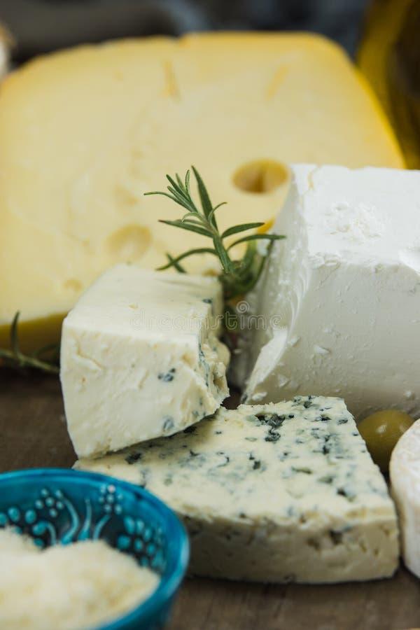 Poco diferente tipo de quesos con las aceitunas papel y el aceite de oliva en la pizarra negra en cocina fotos de archivo