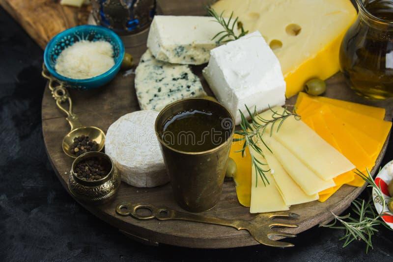 Poco diferente tipo de quesos con las aceitunas papel y el aceite de oliva en la pizarra negra en cocina imagen de archivo