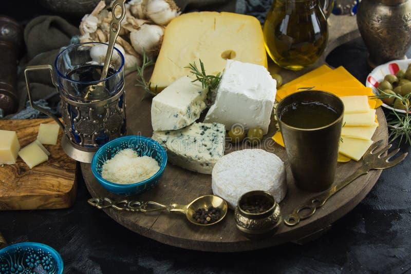 Poco diferente tipo de quesos con las aceitunas papel y el aceite de oliva en la pizarra negra en cocina imagen de archivo libre de regalías