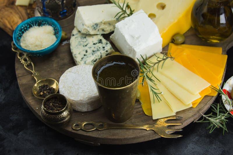 Poco diferente tipo de quesos con las aceitunas papel y el aceite de oliva en la pizarra negra en cocina fotografía de archivo libre de regalías