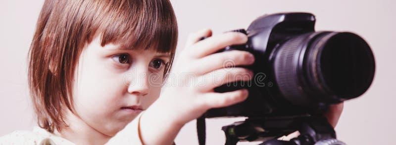 Poco fotógrafo lindo de la muchacha del niño está tomando una foto imagenes de archivo