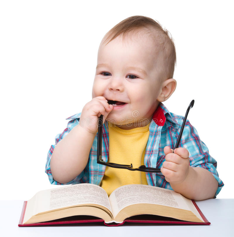 Poco gioco da bambini con il libro ed i vetri immagine stock libera da diritti