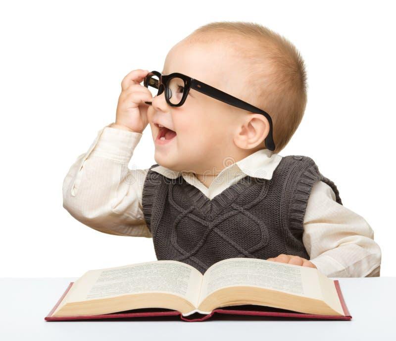 Poco gioco da bambini con il libro ed i vetri fotografia stock