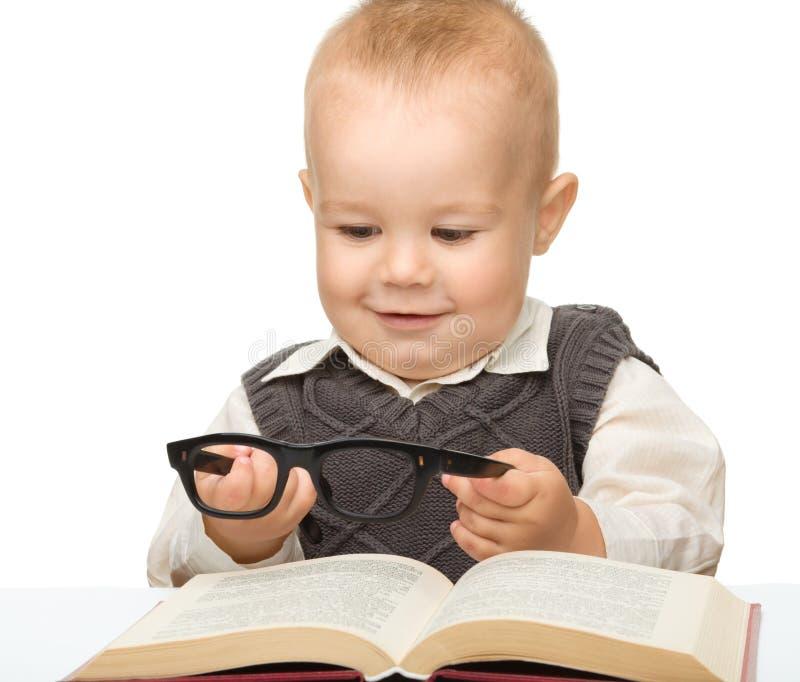 Poco gioco da bambini con il libro ed i vetri immagini stock libere da diritti