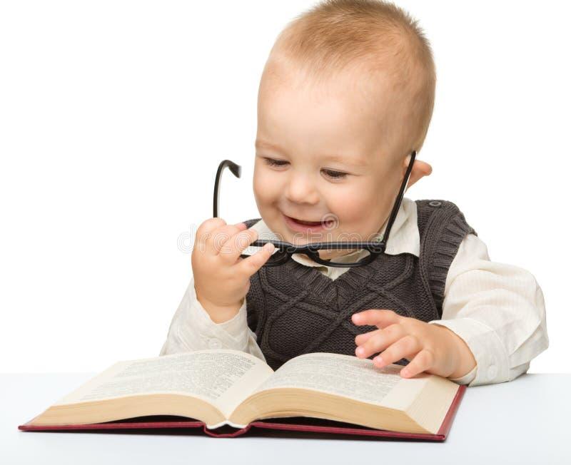 Poco gioco da bambini con il libro ed i vetri fotografia stock libera da diritti