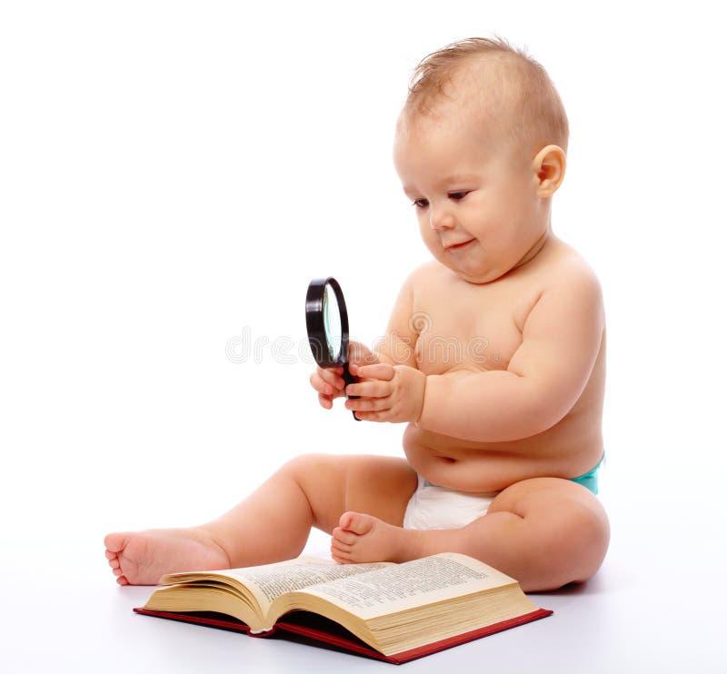 Poco gioco da bambini con il libro ed il magnifier immagini stock libere da diritti