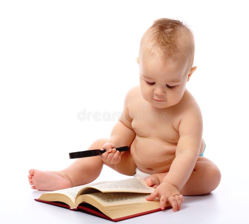 Poco gioco da bambini con il libro ed il magnifier immagini stock