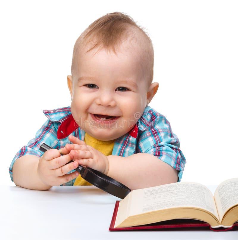 Poco gioco da bambini con il libro ed il magnifier fotografia stock libera da diritti