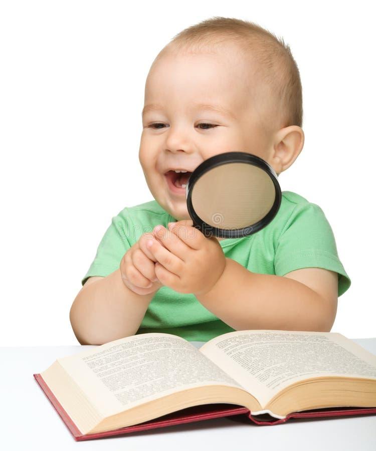 Poco gioco da bambini con il libro ed il magnifier immagine stock libera da diritti