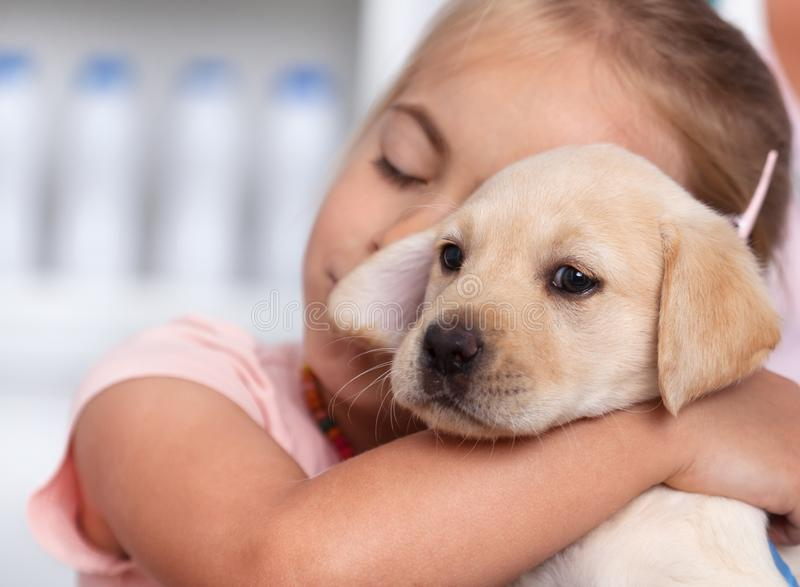 Poco gir que abraza su nuevo perrito que ella acaba de conseguir fotografía de archivo libre de regalías