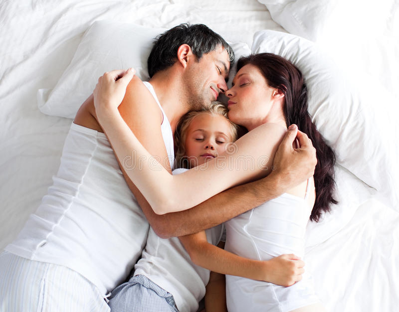 Poco gril que duerme en cama con sus padres fotos de archivo