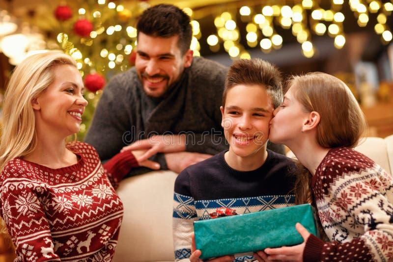 Poco hermana que da a un regalo su más viejo hermano en la Navidad imagen de archivo