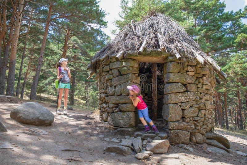 Poco hija que juega escondite con su madre en choza antigua en el bosque de la montaña de Canencia imagen de archivo