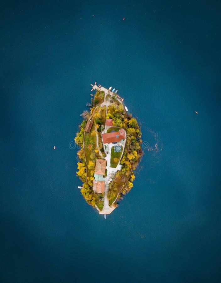 Poco isla acostumbrada en el medio del mar azul foto de archivo